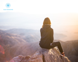 woman looking out at scenery on top of a mountain with blue diamond logo