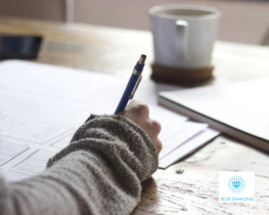 girl writing and planning on paper in office with mug and blue diamond logo